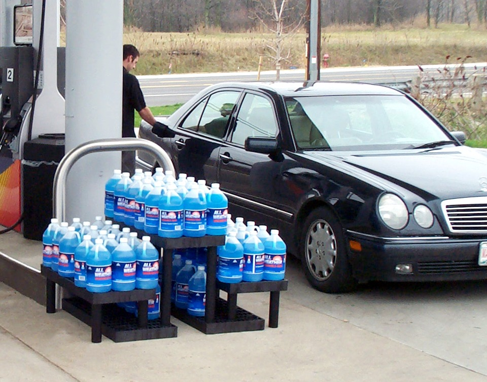 a three-tier plastic display holding antifreeze at a gas station pump