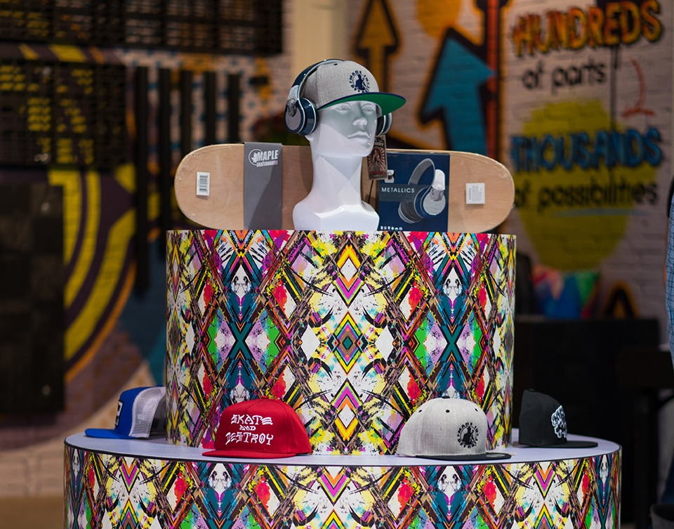 a plastic display stand with mannequin heads and fun wrapping colors