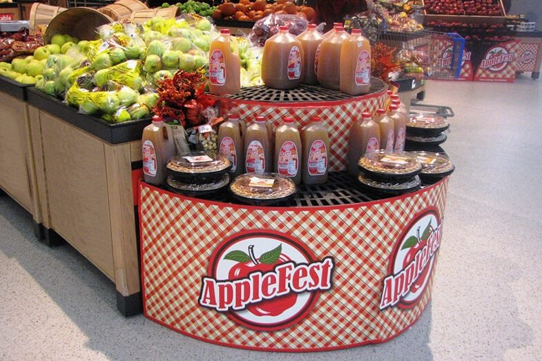 Applefest display with apple cider and pies in a grocery store